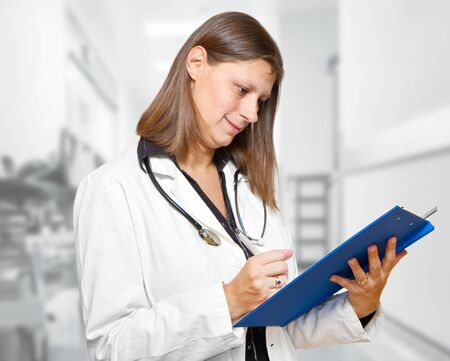 Female doctor looking at medical records in the hospital