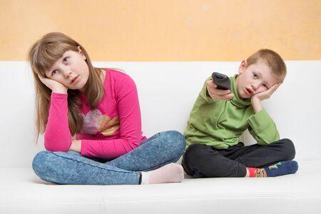 bored children sitting on the couch watch TV during the Coronavirus quarantine