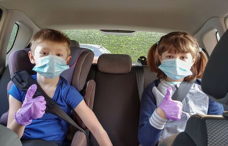 Coronavirus Covid-19 concept.Young brothers wearing face mask protect from virus and thumb up finger gesture for stop corona virus outbreak in the car. coronavirus and pandemic virus symptoms. 写真素材