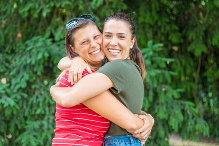Portrait of two young beautiful smiling girls hug each other in a summer day whit colored t-shirt clothes and jeans