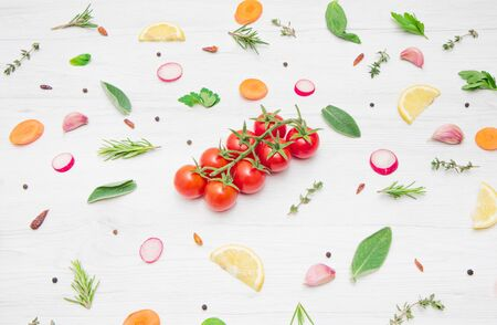 top view of various types of aromatic herb leaves and cut vegetables on wooden background Reklamní fotografie