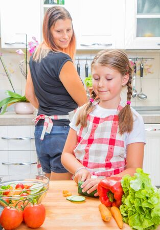Mother and daughter in kitchen are preparing vegetables