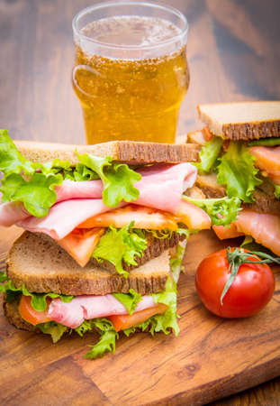 sandwiches with ham and smoked salmon with beer glasses Standard-Bild