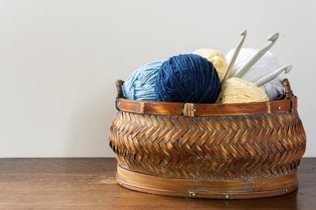 ウールと木製のテーブルの 3 つのかぎ針編みのフックのバスケット 写真素材