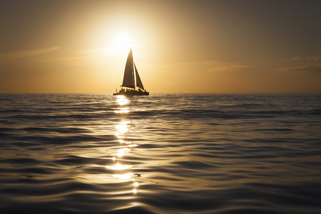 Silhouette of sailboat at shimmering golden sunset on Gulf of Mexico Stock Photo