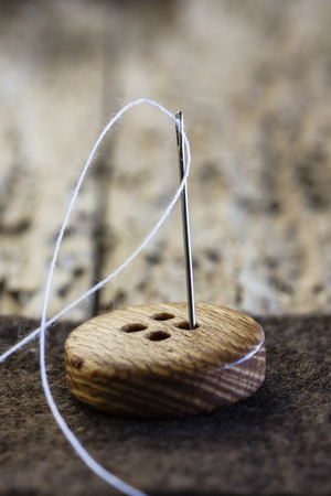 Close up of needle button and thread on rustic background Stock Photo