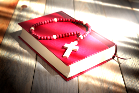 the rosary on the red book illuminated by the sun Stock Photo
