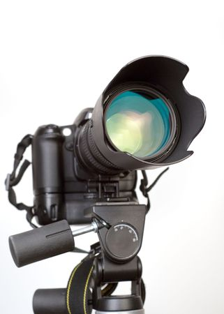 enthusiast: Professional digital SLR camera with telephoto zoom lens on tripod. Isolated white background, focus on lens.