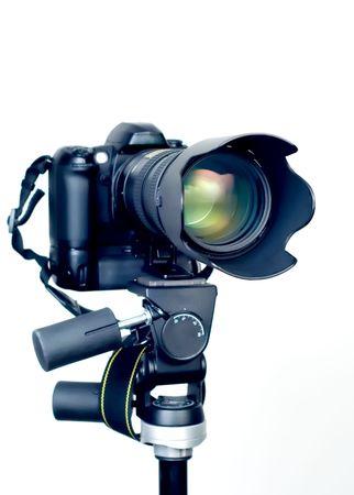 dslr camera: Professional DSLR camera with telephoto zoom lens on tripod.