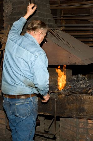 blacksmith shop: Old blacksmith at the forge of old blacksmith shop. Stock Photo