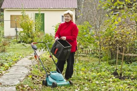 mows: Woman mows grass lawnmower Stock Photo