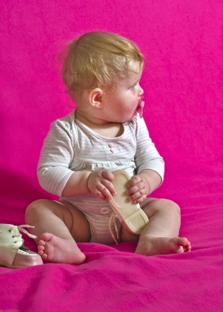 shoeless: barefoot child baby wear shoes while sitting on a pink background Stock Photo