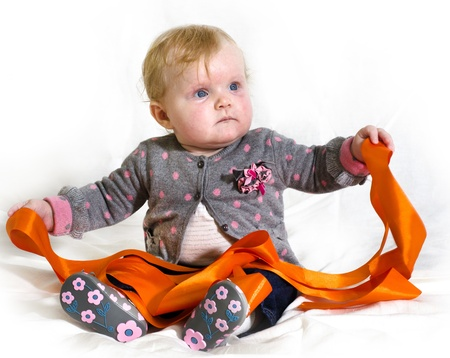 little baby girl playing with an orange ribbon on a white background Stock Photo - 16167102