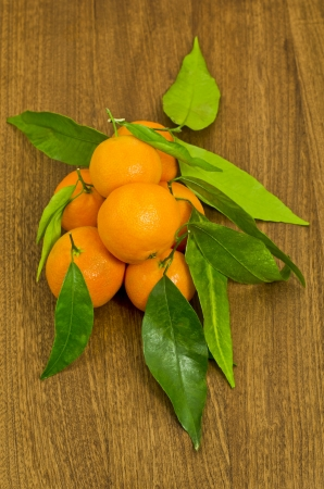 tangerines with leaves in a group on a wooden table top photo