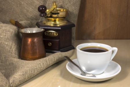 cezve: Coffee in a cup on a marble table, coffee grinder and Cezve Stock Photo