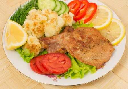 Grilled pork chop with a side dish of cauliflower and vegetables on the plate photo