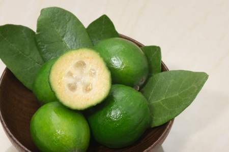 Feijoa fruit and leaves on a marble table Stock Photo
