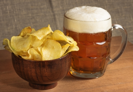 potato chips in a wooden bowl and mug of beer photo