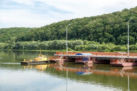 oka: tug boat sets section of pontoon bridge on the river Oka - Russia