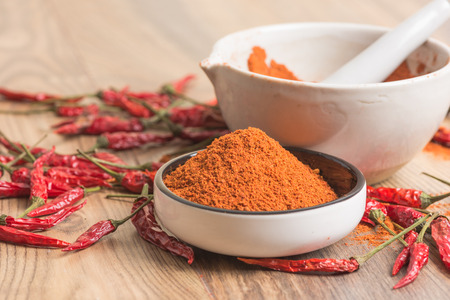 red hot pepper chili powder in a mortar and pods on a wooden table