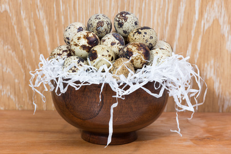 quail eggs lying in a wooden bowl on the table
