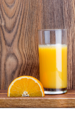slice of orange and a glass of orange juice on a dark wooden table