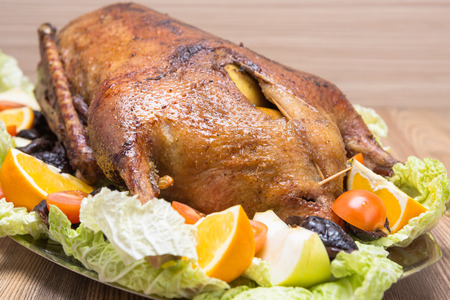 goose roasted with apples and prunes on a platter