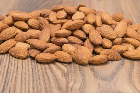 peeled almond nuts on a wooden background