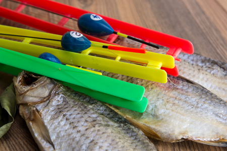 Dried roach - vobla and fishing equipment with a float on a wooden table