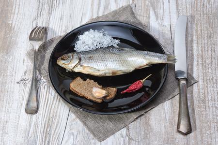 stockfish - roach on a black plate - Vintage installation Stock Photo