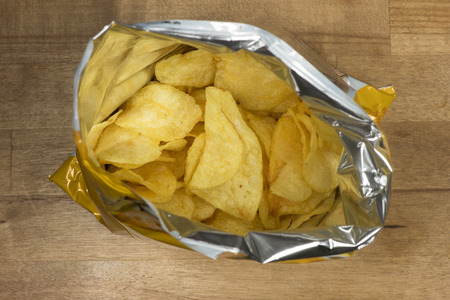 potato chips: potato chips in an open bag on a wooden table