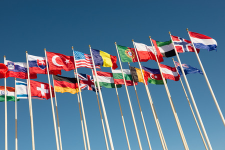 flagpoles: flags of different countries on flagpoles fluttering in the wind Stock Photo