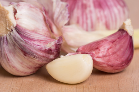 clove plant: garlic - clove and head of garlic on a wooden table