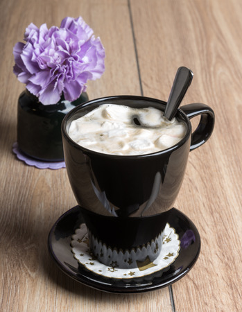 Coffee with marshmallows in a black mug on the wooden table Stock Photo