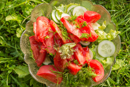 lettuce, tomatoes and cucumbers in a glass bowl on a green grass