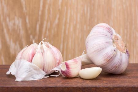 garlic clove: garlic - clove and head of garlic on a wooden table