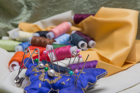 sewing item: needle and thread on background fabrics for sewing