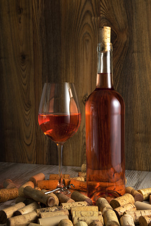 rose wine: Rose wine in a transparent bottle, glass, cork and a corkscrew on the background boards
