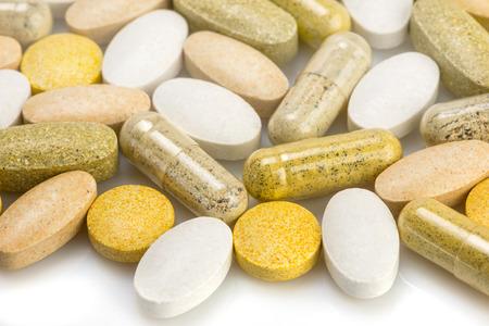 pastillas: Los suplementos vitam�nicos - c�psulas y pastillas sobre una superficie blanca
