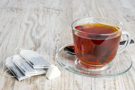 tea bags and transparent cup with tea on a table of old boards Stock Photo