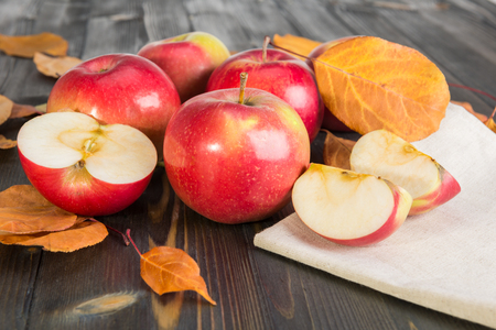 red winter apples and dry leaves on a wooden table
