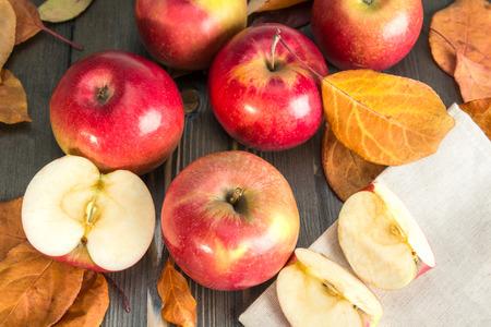 hojas secas: las manzanas de invierno rojas y hojas secas sobre una mesa de madera