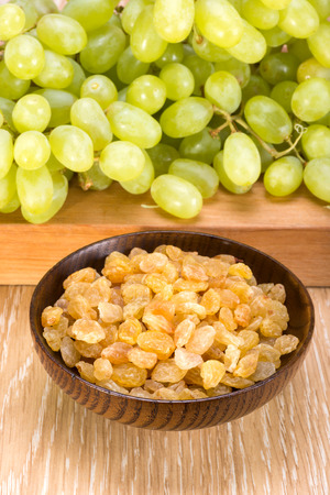 seedless: white seedless grapes and raisins sultanas  in a wooden bowl Stock Photo