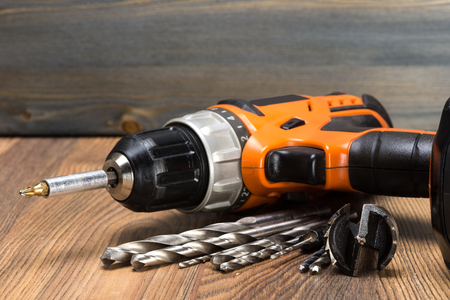 turning table: battery powered drill and drill on a wooden surface