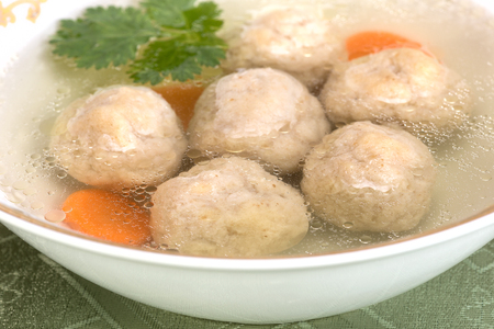 kneidl: A traditional Ashkenazi Jewish soup with bolls, made from a mixture of matzah meal, eggs, water, and fat, boiled in chicken bouillon Stock Photo