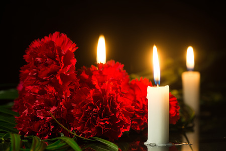 candles and red flowers on a black marble slab