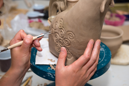 working hands: potter produces ceramic ware out of clay - handmade