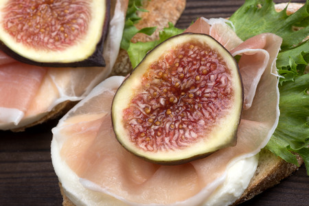 cured: Bruschetta - Grilled bread topped with cured meat (prosciutto) and figs