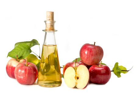 apple cider vinegar in a glass vessel and red apples isolated on white background