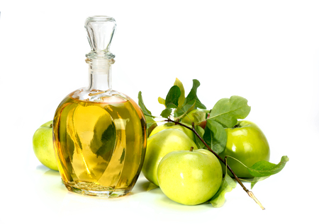 apple cider vinegar in a glass vessel and green apples isolated on white background